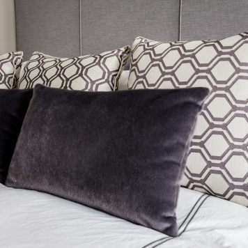 Velvet and patterned pillows on bed