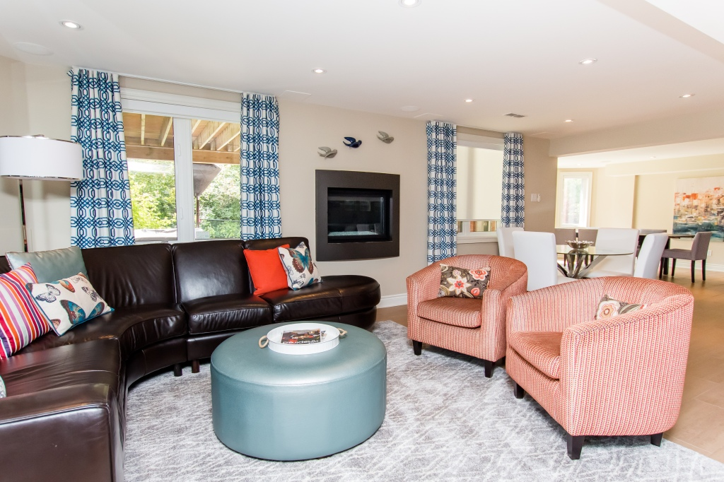 Brown leather couch with blue ottoman and two orange chairs