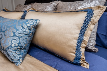 customized blue and gold pillows in bedding showroom